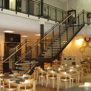Raka trappor design – Trappa med terrazzosteg, räcke med nät och trähandledare.