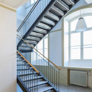 Raka trappor interiört – Rak trappa med betongsteg och trähandledare.